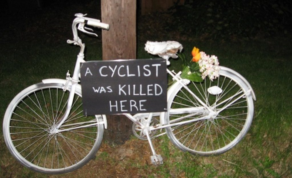 "Ghost Bike with sign ""A Cyclist Was Killed Here"""