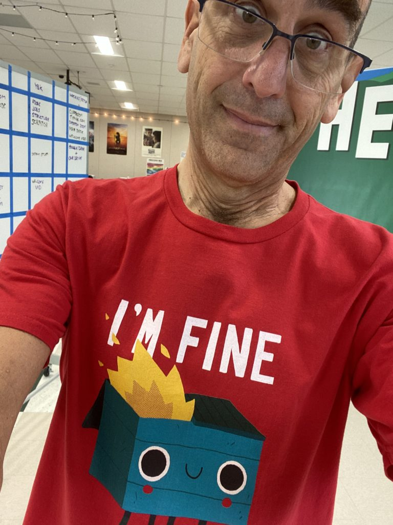 "Me wearing a shirt with a cartoon dumpster on fire saying ""I'M FINE."""